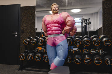 Proud man wearing pink bodybuilder costume in gym - GUSF03288