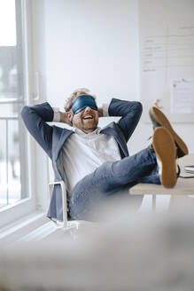 Businessman having a power nap at desk in office - GUSF03297