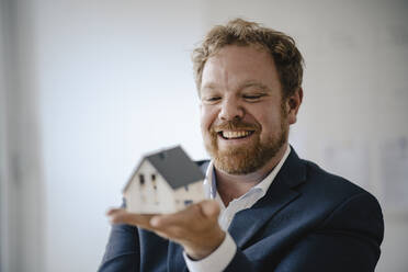 Happy businessman holding model house in office - GUSF03300