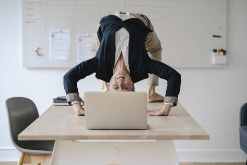 Young businesswoman practicing yoga on desk in office - GUSF03312