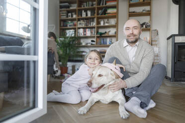 Portrait of father sitting with his little daughter and the dog on the floor at home - KMKF01201