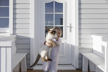 Little girl carrying cat on her arms in front of house entrance - KMKF01210