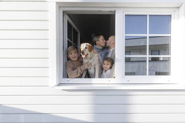 Happy family with two children and a dog at opened window of their house - KMKF01213
