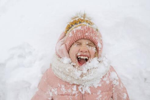 Portrait of screaming girl lying on snow - EYAF00853