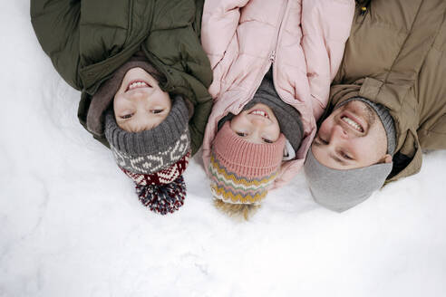 Family portrait of father and two children lying on snow - EYAF00856