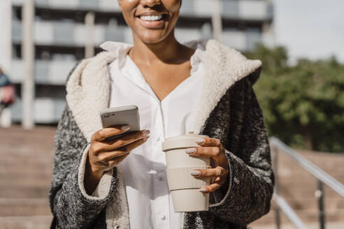 Stylish businesswoman commuting in the city, carrying smartphone and coffee cup - AFVF05079