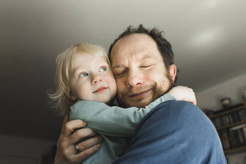 Affectionate father carrying little daughter at home - IHF00260