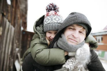 Portrait of father carrying daughter piggyback outdoors in winter - EYAF00864