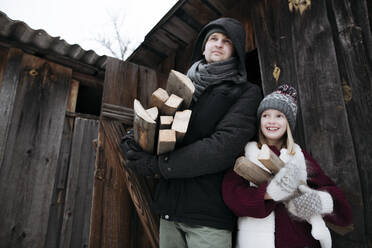 Happy father and daughter holding firewood in winter - EYAF00873