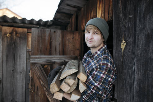 Portrait of man wearing wooly hat carying firewood - EYAF00876