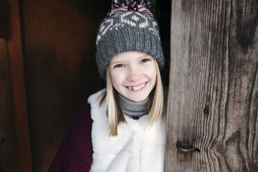 Portrait of happy girl wearing woolly hat at wooden wall - EYAF00885