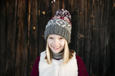 Portrait of happy girl wearing woolly hat at wooden wall - EYAF00891