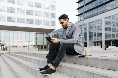 Casual young businessman sitting on stairs in the city using tablet - JRFF03973