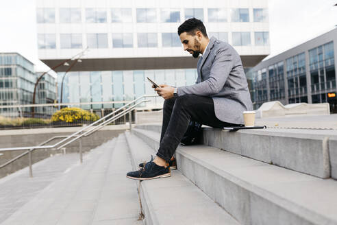 Casual young businessman sitting on stairs in the city using tablet - JRFF03976