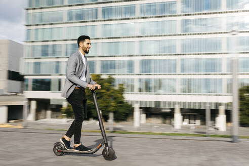 Casual young businessman riding electric scooter in the city - JRFF03994
