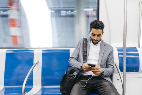 Young businessman with cell phone and earphones on the subway - JRFF04006