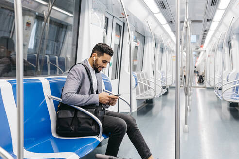 Young businessman with cell phone and earphones on the subway - JRFF04009