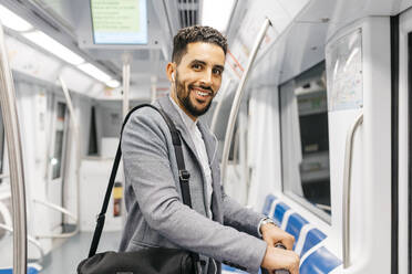 Portrait of smiling young businessman with earphones on the subway - JRFF04015