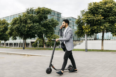 Casual young businessman with electric scooter talking on the phone in the city - JRFF04024