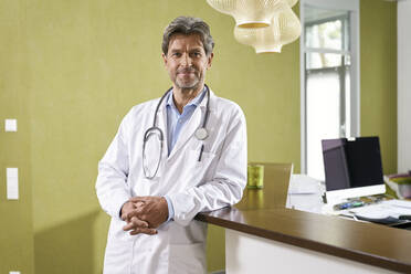 Portrait of confident doctor at reception in his medical practice - PHDF00033