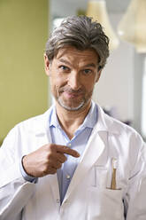 Portrait of dentist pointing at toothbrush in his pocket - PHDF00036