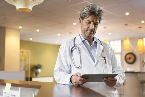 Doctor using tablet at reception in his medical practice - PHDF00045
