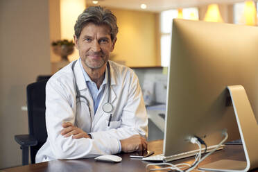 Portrait of confident doctor at desk in his medical practice - PHDF00051