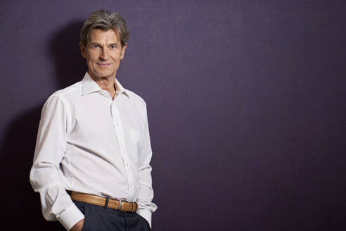 Portrait of confident businessman in front of a purple wall - PHDF00072
