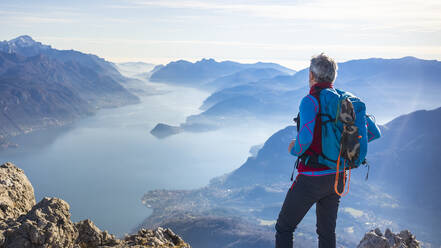Hiker standing on mountain, looking at Lake Como, Italy - MCVF00193