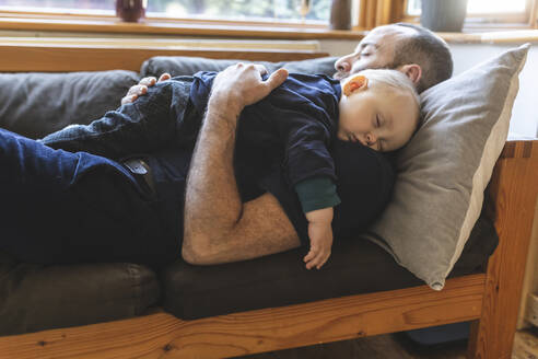 Father and son sleeping together on the sofa - WPEF02483