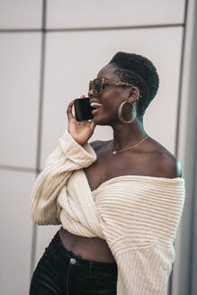 Portrait of laughing young woman on the phone wearing sunglasses - MPPF00445