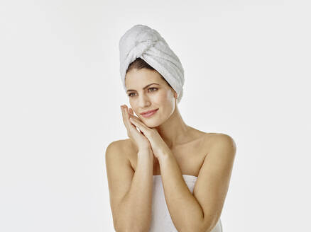 Portrait of smiling woman with hairs wrapped in towel against white background - RORF01992