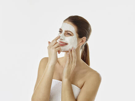 Portrait of smiling woman with beauty mask in front of white background - RORF02004