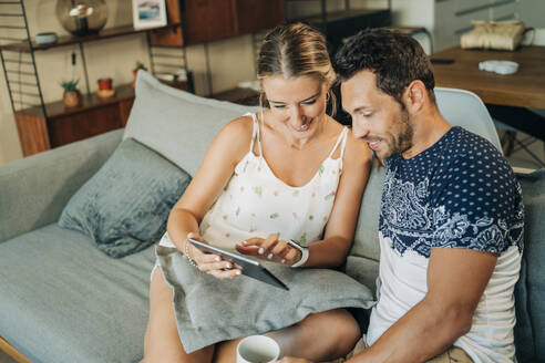 Happy relaxed couple sitting on couch in living room sharing a tablet - MPPF00459