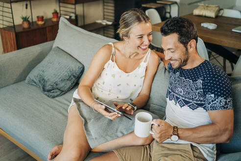 Happy relaxed couple sitting on couch in living room sharing a tablet - MPPF00462