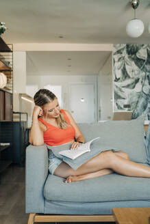 Relaxed woman sitting on couch in living room reading book - MPPF00474
