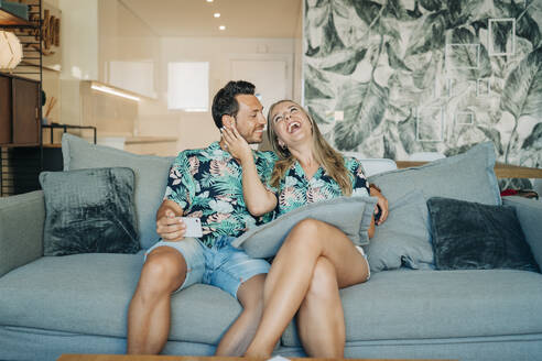 Happy couple sitting on couch in living room wearing Hawaiian shirts - MPPF00486