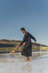 Young man wearing black kaftan performing outdoors in a puddle - AFVF05198