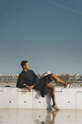 Young man wearing black kaftan lying on a wall - AFVF05201