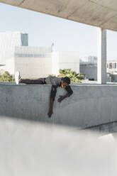 Young man wearing black kaftan climbing on a concrete wall - AFVF05204