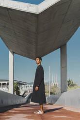 Young man wearing black kaftan standing on a footbridge - AFVF05207