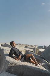 Young man wearing black kaftan lying on concrete blocks under blue sky - AFVF05210