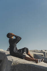 Young man wearing black kaftan sitting on concrete blocks under blue sky covering his face - AFVF05213