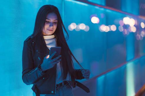 Portrait of smiling teenage girl leaning against blue glass pane looking at smartphone - DLTSF00421