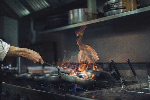 Chef preparing a flambe dish at gas stove in restaurant kitchen - OCAF00437
