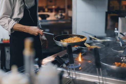 Chef cooking pasta in Italian restaurant kitchen - OCAF00440