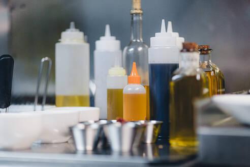 Detail of spicy oil bottles in restaurant kitchen - OCAF00461