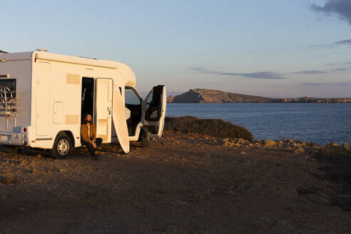 Man sitting at opened car door of camper enjoying sunlight, Es Mercadal, Menorca, Spain - JPTF00453