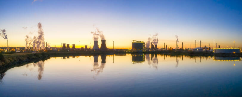 UK, Scotland, Grangemouth, Cooling towers of Grangemouth Refinery reflecting in coastal water of Firth of Forth at sunset - SMAF01729