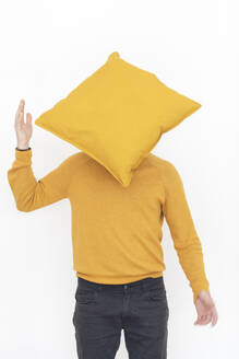 Man wearing yellow pullover hiding face behind yellow cushion - MCVF00198